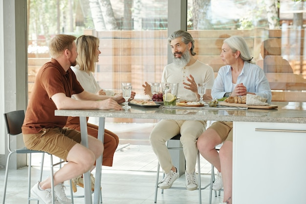 Senior father with gray beard sitting at counter table and gesturing hands while sharing news with grown kids during family dinner