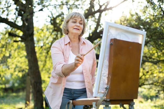 公園で晴れた日に夏の暖かい気候を楽しみながら、キャンバスに絵を描くシニア女性アーティスト。屋外での絵画、趣味、芸術のコンセプト。