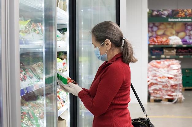 보호 의료 마스크와 고무 장갑을 끼고 슈퍼마켓에서 고위 여성 고객
