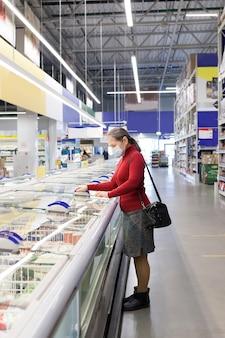 보호 의료 마스크를 착용하는 슈퍼마켓에서 고위 여성 고객