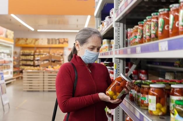 Старший клиент-женщина делает покупки в супермаркете в защитной медицинской маске