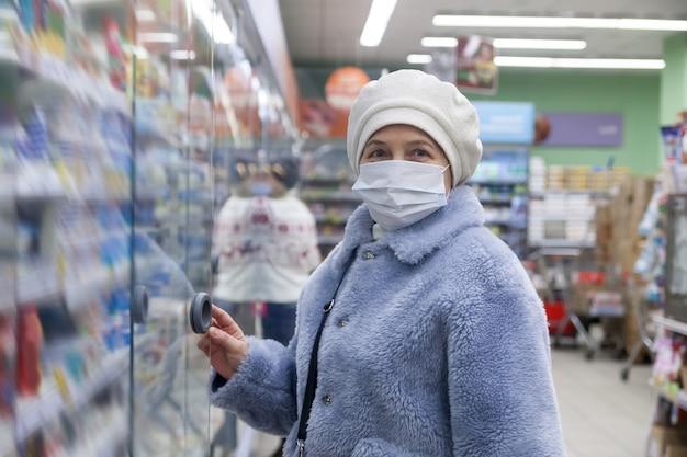保護医療マスクを身に着けているスーパーマーケットで買い物かごを持つシニア女性顧客