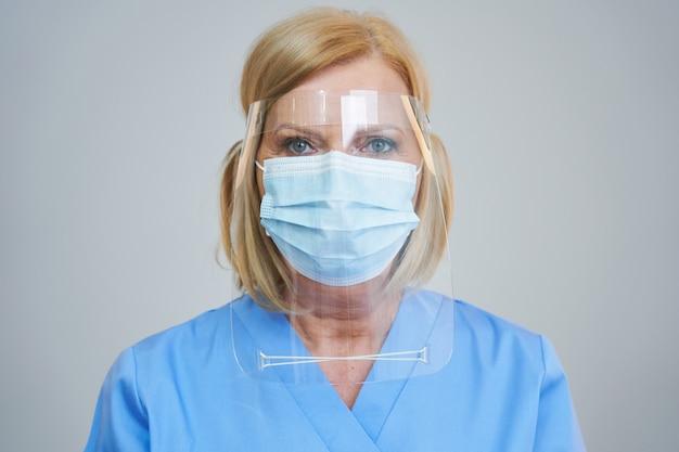 灰色の背景の上のマスクと盾でポーズをとってシニア女性医師