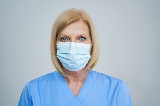 灰色の背景の上のマスクでポーズをとってシニア女性医師