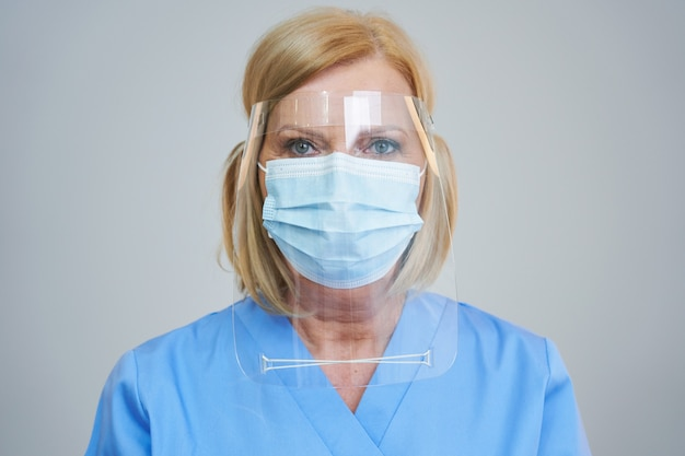Senior female doctor posing in mask and shield over gray background