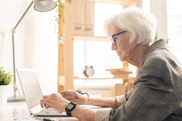 Senior female in eyeglasses bending over laptop while searching in the net for online video about healthcare issues