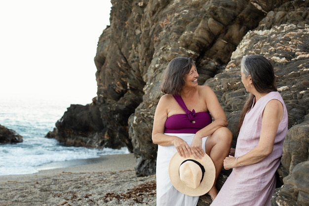 Senior female friends spending time together on the beach
