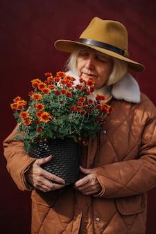 Старший садовник в верхней одежде, осматривает букет цветов в горшках на бордовом фоне.