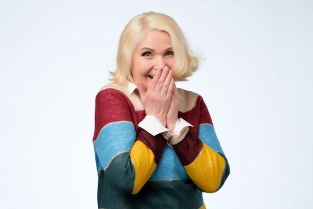 年配の女性は嬉しそうに笑い、笑いをやめようと口を覆います
