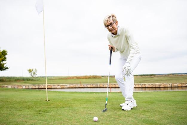 トレーニング中に膝の怪我と痛みを抱えているシニア女性ゴルフ選手。