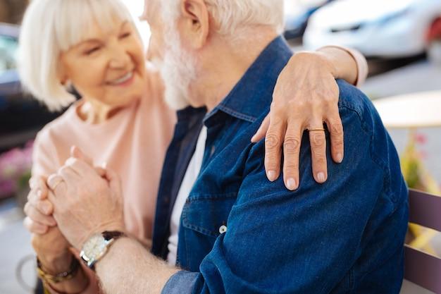Senior female hand wearing wedding ring and hugging man