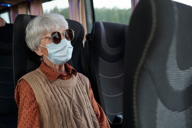 Старшая женщина в солнцезащитных очках повседневной одежды и защитной маске