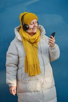 음악을 듣고 스마트폰을 사용하는 시니어 여성.