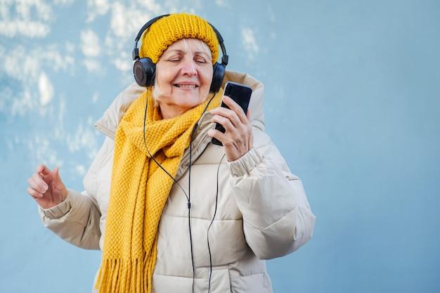 음악을 듣고 스마트폰을 사용하는 시니어 여성. 프리미엄 사진