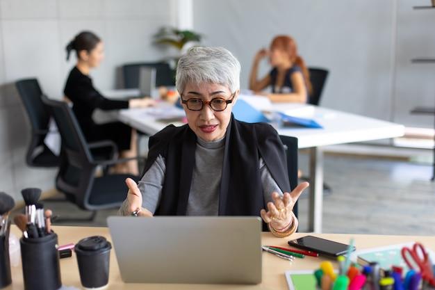 Старший женский визажист обучения онлайн-класс на портативном компьютере в домашнем офисе.