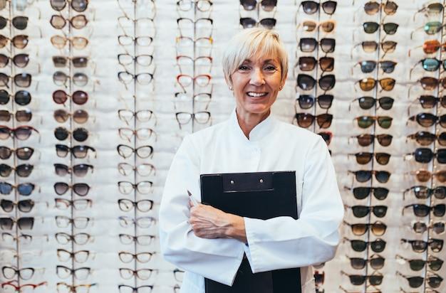 光学店に立っているシニア女性眼科医。