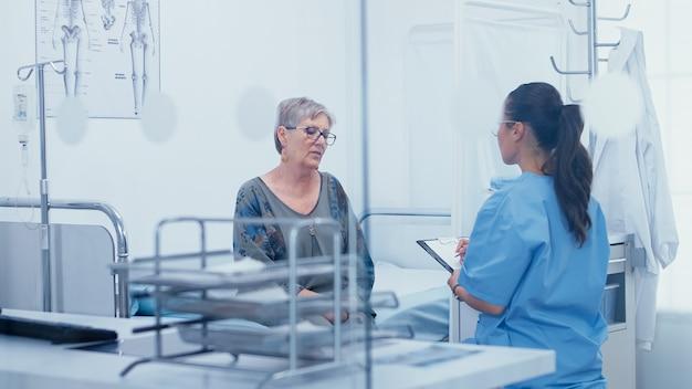 병원 침대에서 간호사와 수석 여성 환자 이야기. 현대 병원 또는 개인 클리닉의 건강 관리, 진료실 치료 약물 진단 전문 지식의 질병 예방 및 상담