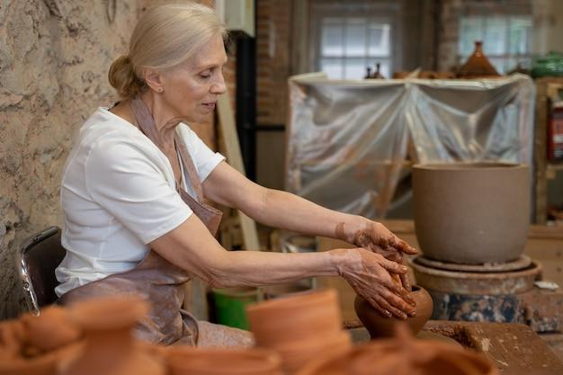 Старшая гончарша лепит глиняный горшок, скульптор работает с глиной на гончарном круге и за столом