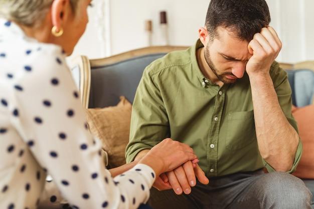 치료 세션 동안 고통받는 젊은 남자에게 전문적인 도움을 제공하는 수석 여성 심리 치료사