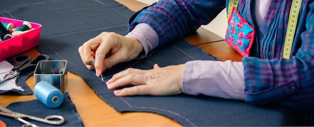 Старшая швея шьет ткань, чтобы сшить одежду в своей мастерской