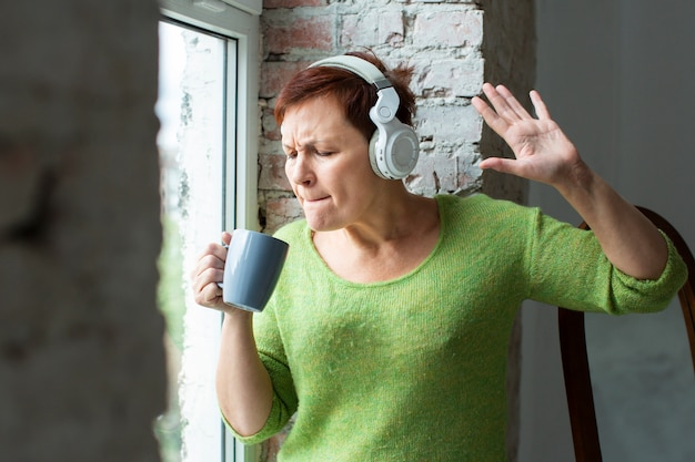 Senior female singing at coffee mug