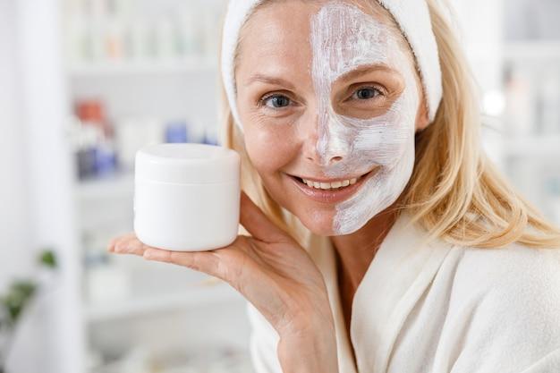 ビューティーサロンで顔の半分に化粧マスクをした年配の女性。女性は微笑んで、顔のマスクのブートルを保持します。