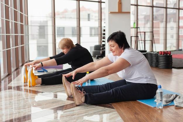 Senior females at gym stretching