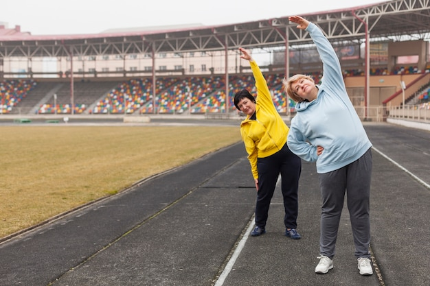 Senior females on stadium stretching