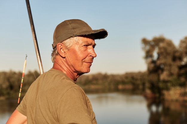 Senior fisher fishing during hot summer day, sitting looking aside, wearing t shirt and cap, posing at bank of river with fishing rod in hand, having rest outdoors.