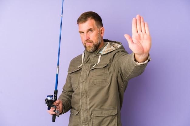 一時停止の標識を示す差し出された手で紫色の背景に立って、あなたを防ぐシニア漁師。