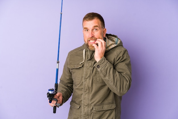 神経質で非常に心配な爪をかむ紫の壁に分離された上級の漁師。