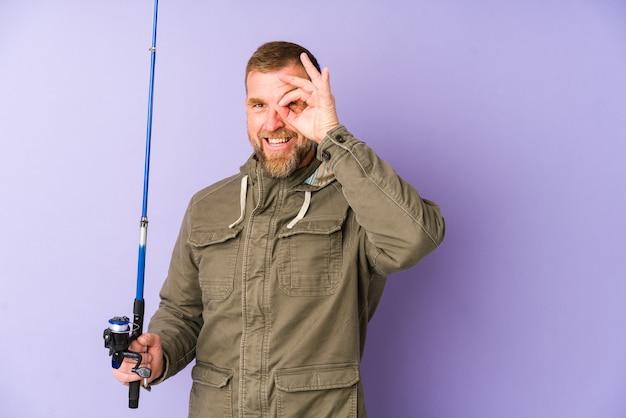 紫色の壁に分離された上級の漁師は目にokのしぐさを維持して興奮しています。