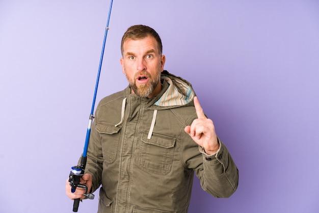 アイデアを持つ紫色の壁に分離された上級漁師