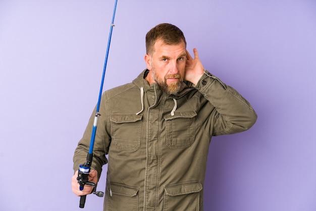 ゴシップを聞いてみようと紫の壁に分離された上級の漁師。
