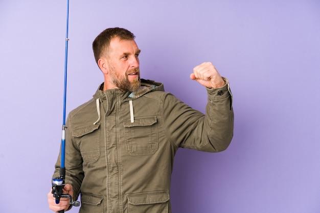 勝利後の拳を上げる紫色の壁にシニアの漁師