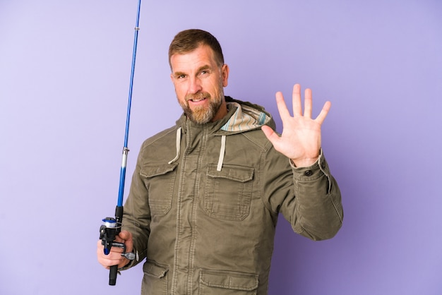指で陽気な表示番号5を笑顔紫の壁にシニアの漁師。
