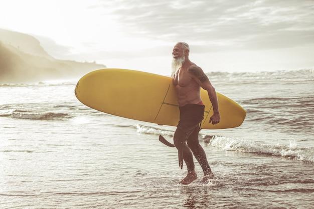 日没でサーフィンした後ロングボードで歩くシニアフィット男-熱帯のビーチでエクストリームスポーツを楽しんで成熟した刺青の男-うれしそうな高齢者のライフスタイルと旅行のコンセプト-男性の体に焦点を当てる