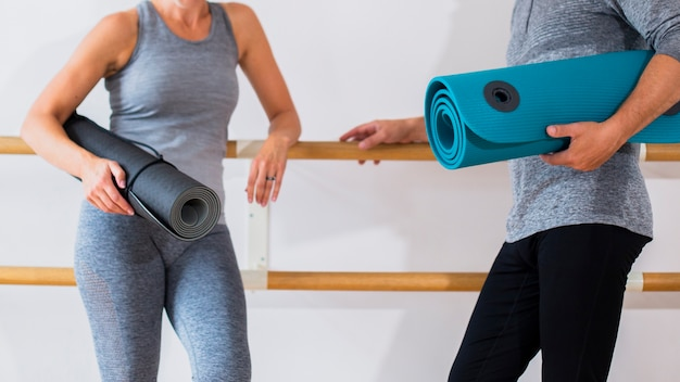 Senior fit man and woman holding yoga mats