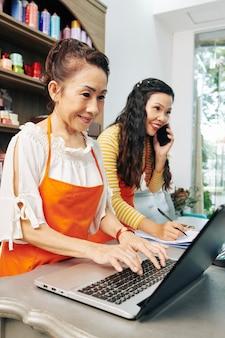 젊은 동료가 고객과 통화 할 때 꽃집 웹 사이트의 양식을 통해 주문을 수락하는 수석 플로리스트