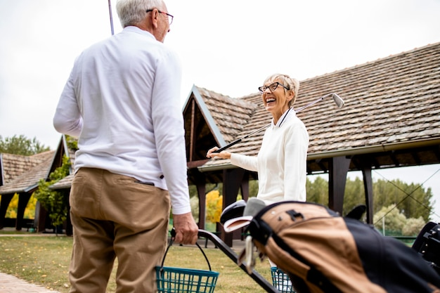Старшие друзья несут снаряжение для гольфа на поле и вместе играют в гольф.