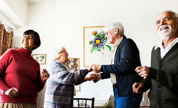 Senior friends dancing together at home