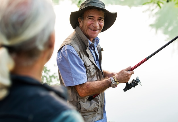 Senior friends fishing by the lake