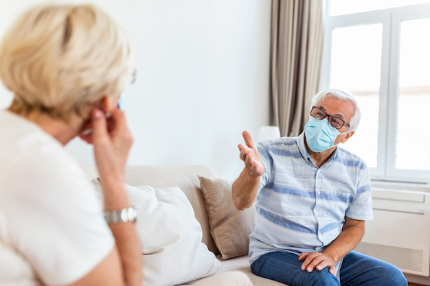 Senior friends having conversation on the sofa at home during covid 19 pandemic