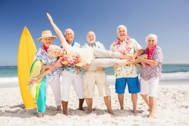 Senior friends holding senior woman