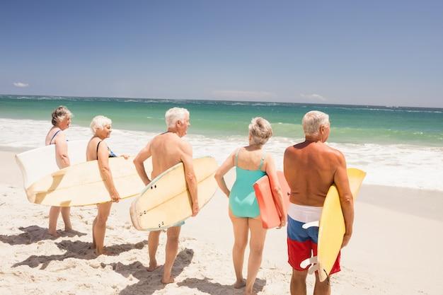 Senior friends holding surfboard