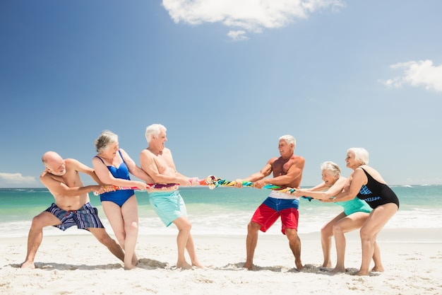 Senior friends playing tug of war