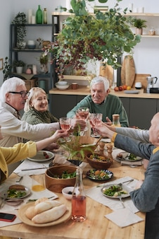 Senior friends sitting at the table and raising glasses of red wine during dinner at home