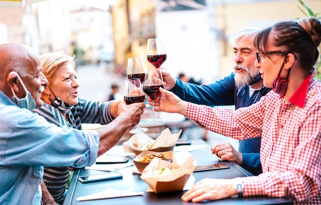 Senior friends toasting red wine at winery bar dehor with open face mask