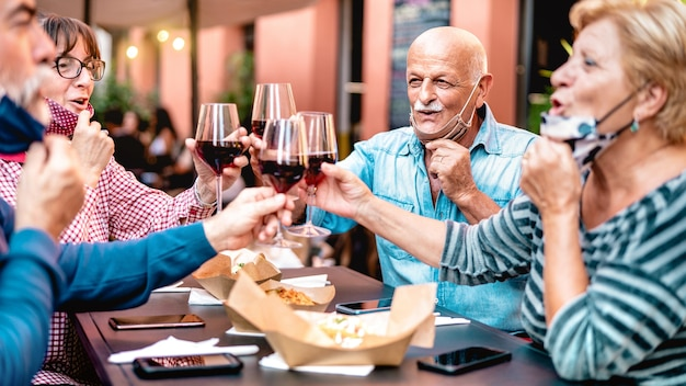 Senior friends toasting wine at restaurant bar wearing opened face mask - focus on bald man