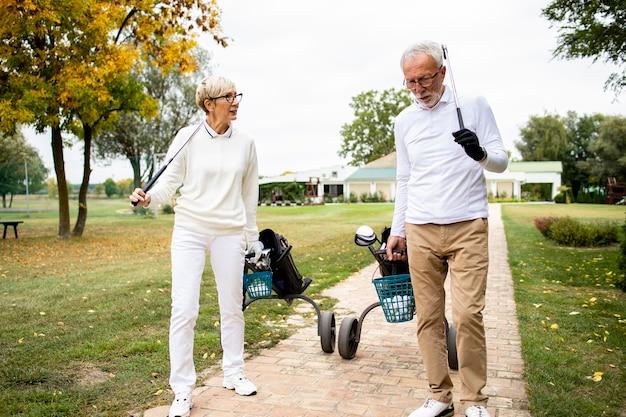 골프 장비를 들고 골프 코스로 걸어가는 선배들.